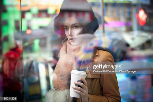 Woman having coffee on city street