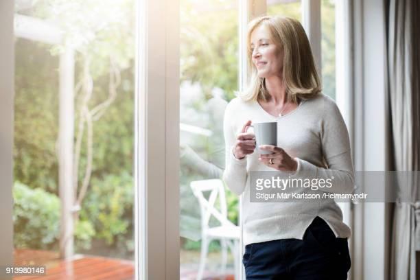 vrouw met koffie terwijl u door het venster - 50 54 jaar stockfoto's en -beelden