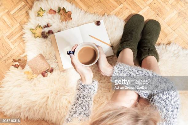 Woman Having Coffee While Sitting On Rug