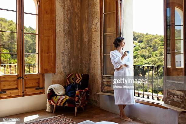 Woman having coffee while standing at window