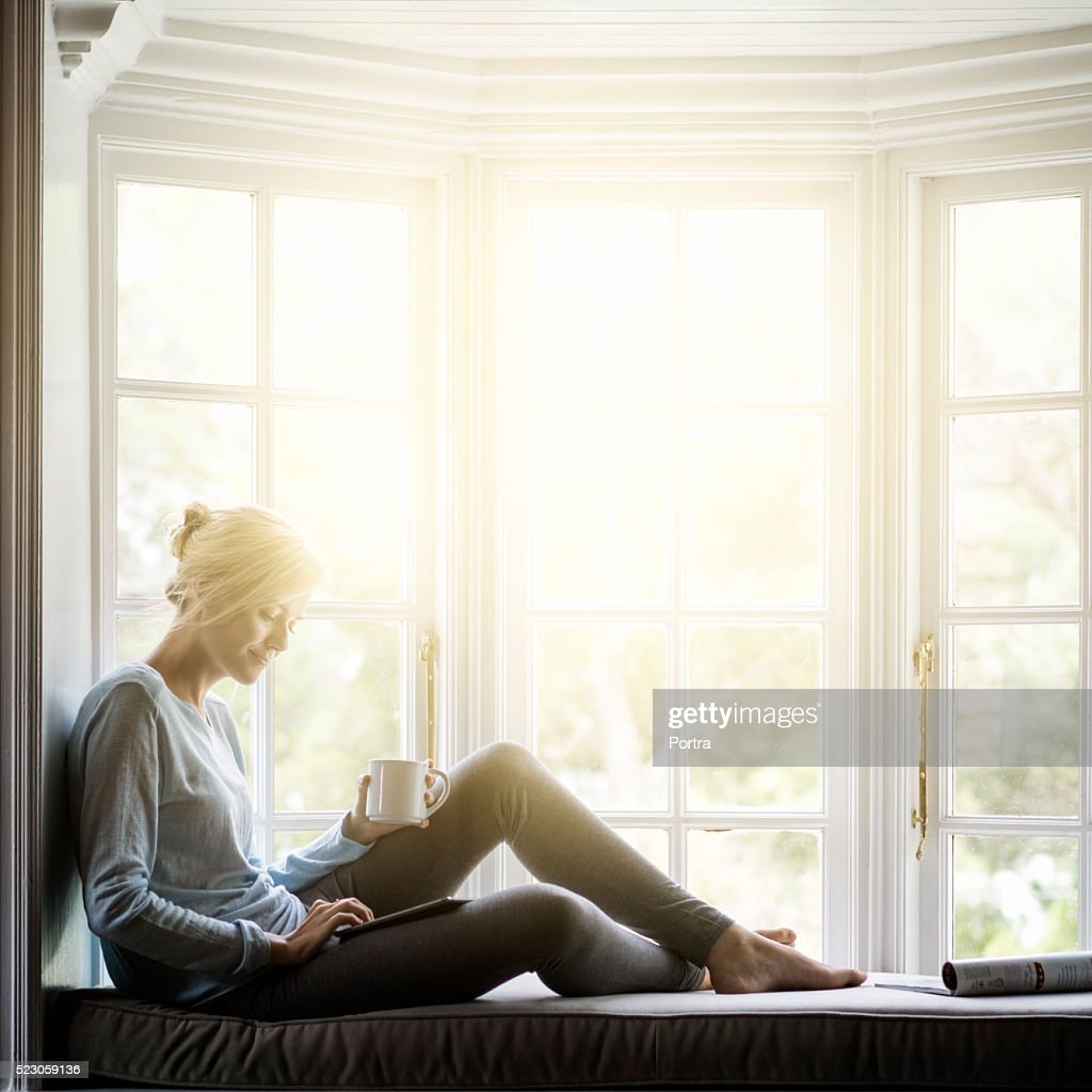 Woman having coffee while using digital tablet on window sill : Stock Photo
