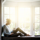 Woman having coffee while using digital tablet on window sill