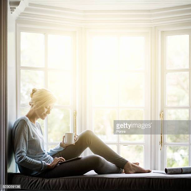 woman having coffee while using digital tablet on window sill - sunny stock pictures, royalty-free photos & images