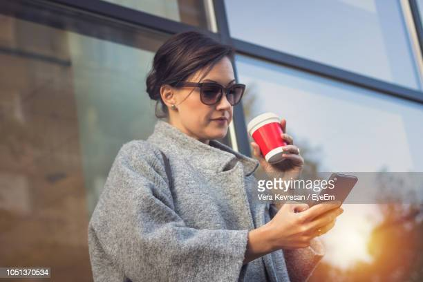 woman having coffee while using mobile phone in city - mid adult women stock pictures, royalty-free photos & images