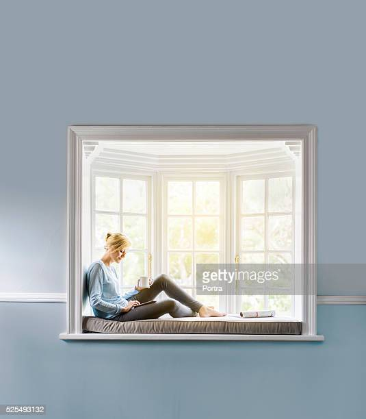 Woman having coffee while using tablet PC on window sill
