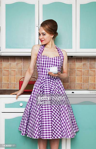 woman having cup of coffee in kitchen - checked dress stock pictures, royalty-free photos & images