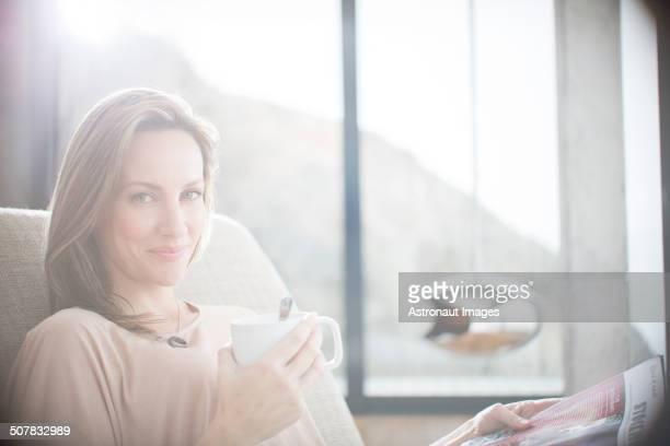 Woman having cup of coffee on sofa