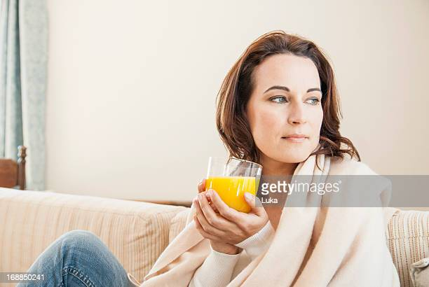 woman having cup of juice on sofa - vitamin c stock pictures, royalty-free photos & images