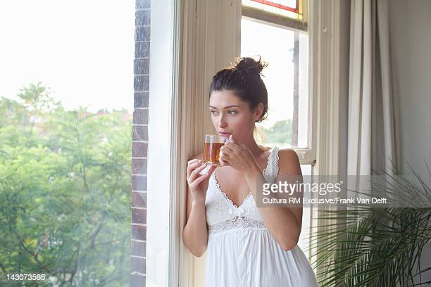 Woman having cup of tea at window
