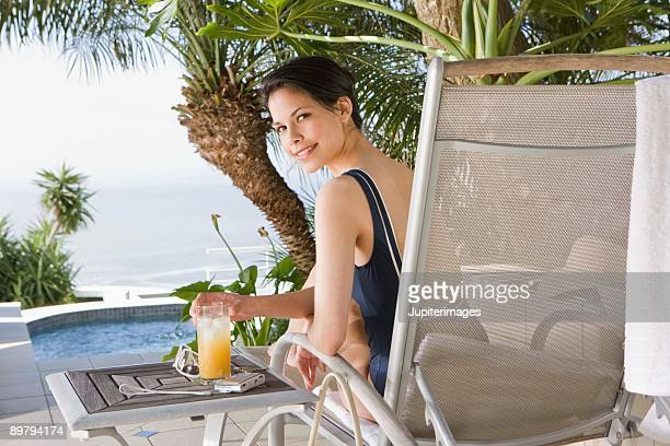 Woman having drink and sitting in chair by swimming pool