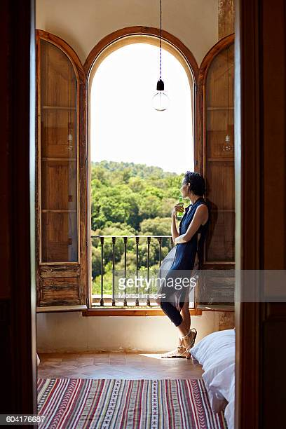 Woman having drink while looking through window