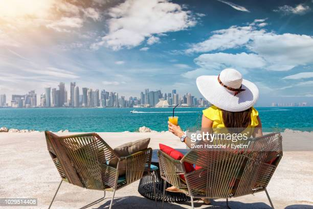 woman having drink while sitting at beach in city - qatar photos et images de collection