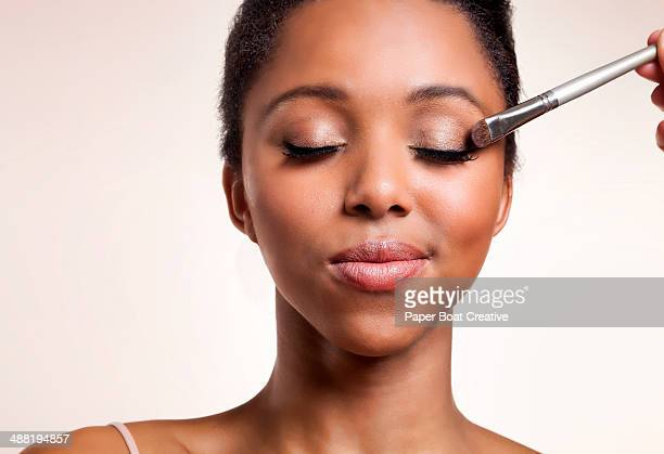 Woman having eyeshadow applied on her face