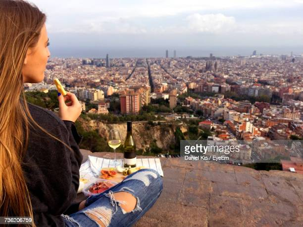 Woman Having Food And Wine While Sitting At Bunkers Del Carmel Against Cityscape