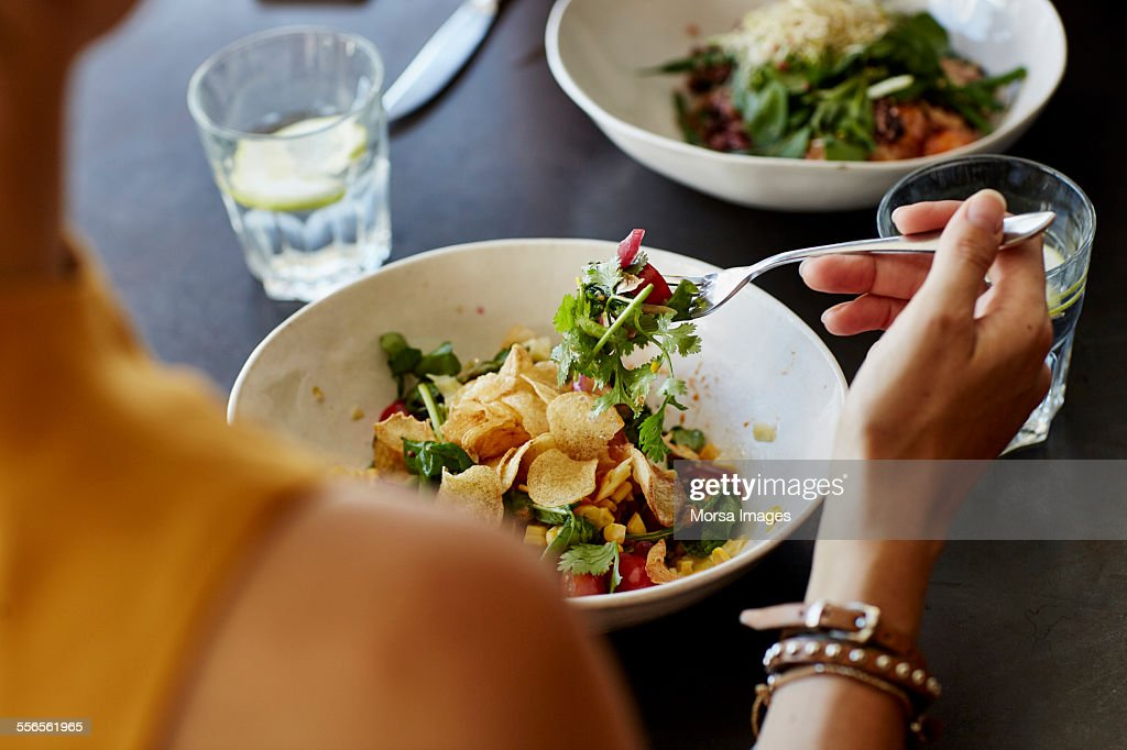 Woman having food at restaurant table : Stock Photo