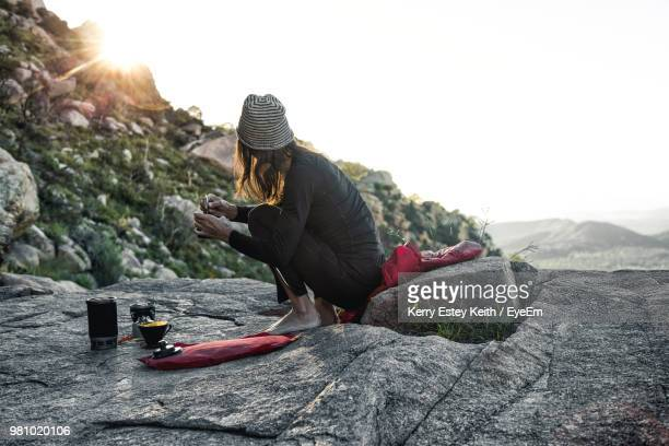 woman having food while sitting on rock against sky - kerry estey keith stock photos and pictures