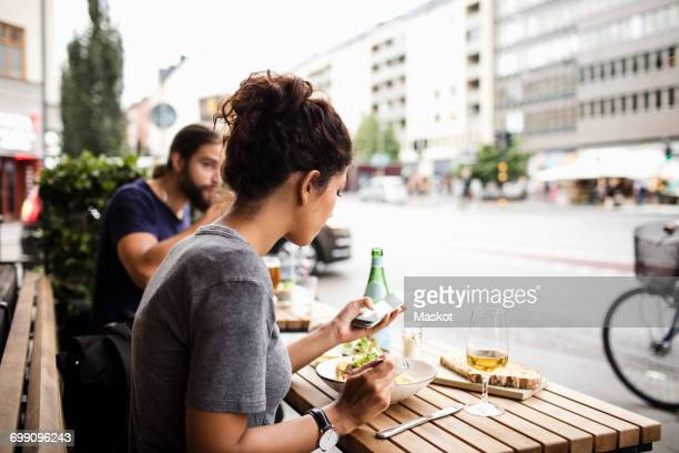 woman having food while using mobile phone at sidewalk cafe in city - café de calçada - fotografias e filmes do acervo