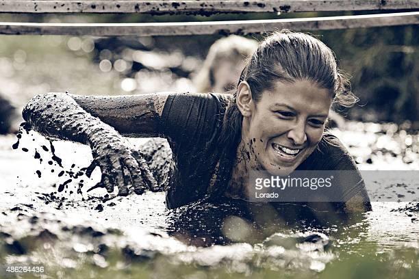 woman having fun crawling in mud