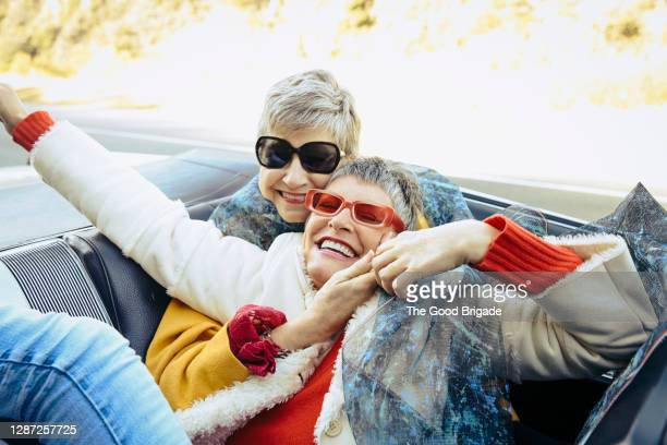 woman having fun in the back of a convertible - female friendship stock pictures, royalty-free photos & images