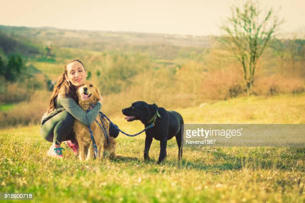 woman having fun in the nature with two dogs