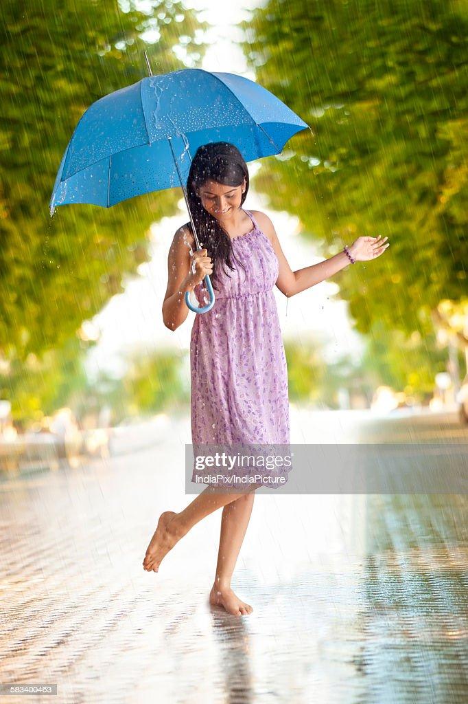 Woman having fun in the rain : Stock Photo
