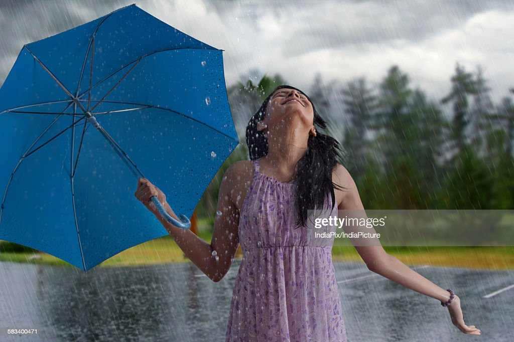 Woman having fun in the rain : Stock Photo