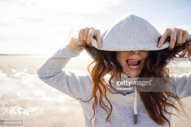 woman having fun on a windy beach, wearing hood - lengua humana fotografías e imágenes de stock