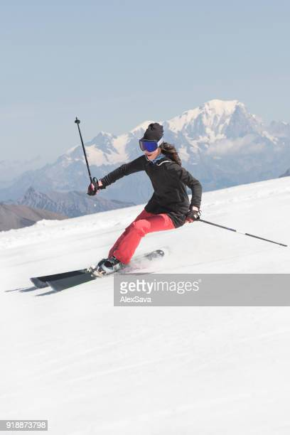 Woman having fun while skiing downhill snow-capped slope