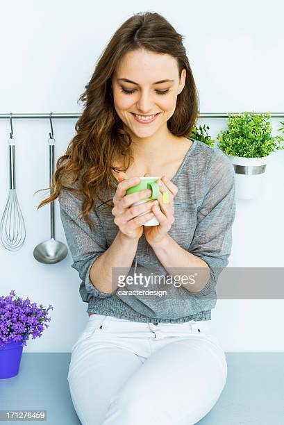 Woman having green tea in her loft