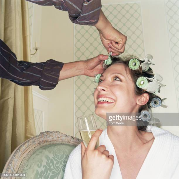 Woman having hair put in rollers, holding champagne flute, looking up