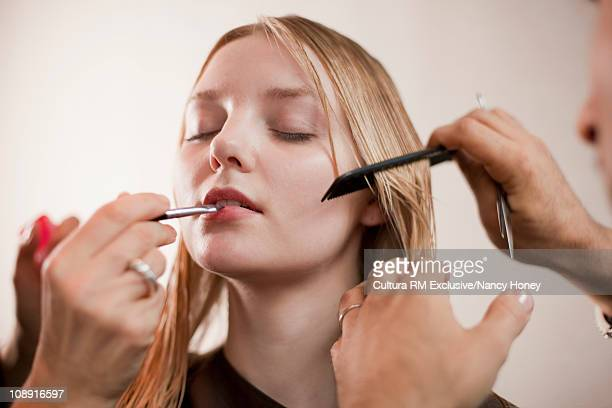Woman having haircut and being made up