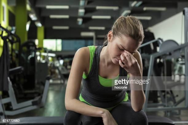 Woman having headache after working out in a health club