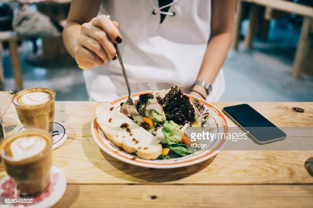 Woman having healthy lunch and coffee in restaurant, and smartphone on tabletop