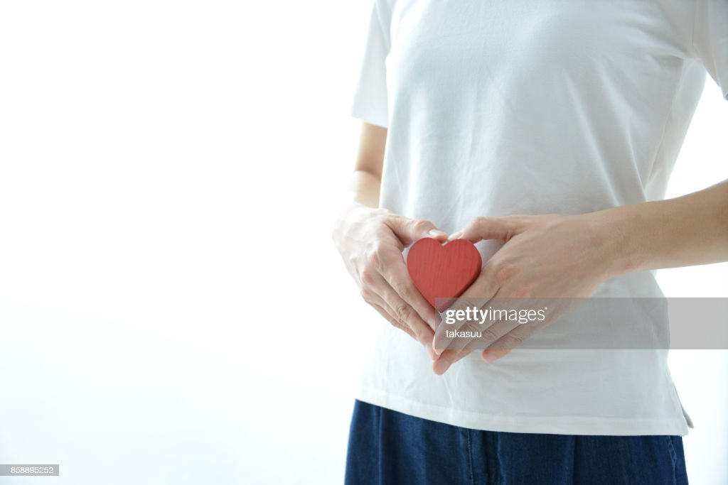 Woman having heart on stomach : Stock Photo