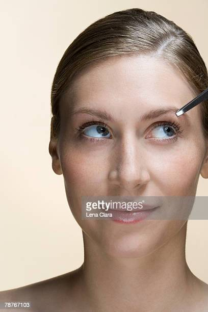 A woman having her eyebrows plucked