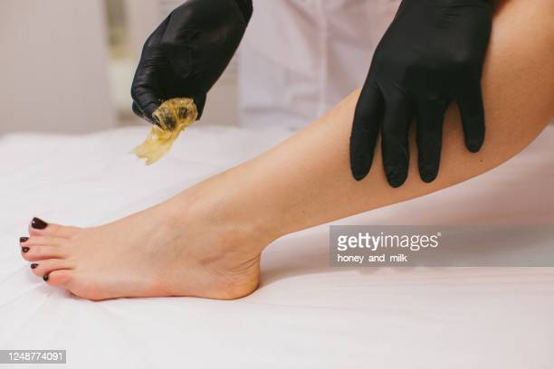 woman having her leg waxed in a beauty salon - leg waxing stock pictures, royalty-free photos & images