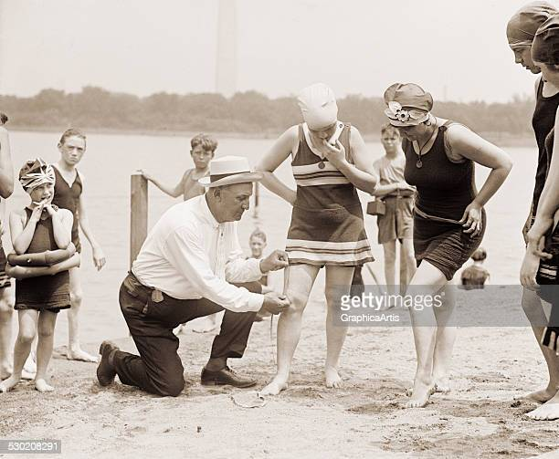 Woman having her swimsuit measured for length violations on a Washington DC beach in the 1920s 1922