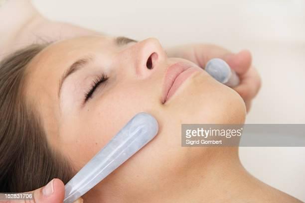 woman having hot stone massage in spa - sigrid gombert stock-fotos und bilder