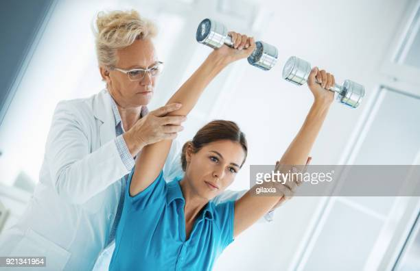 woman having light rehabilitation exercise. - sports medicine stock pictures, royalty-free photos & images