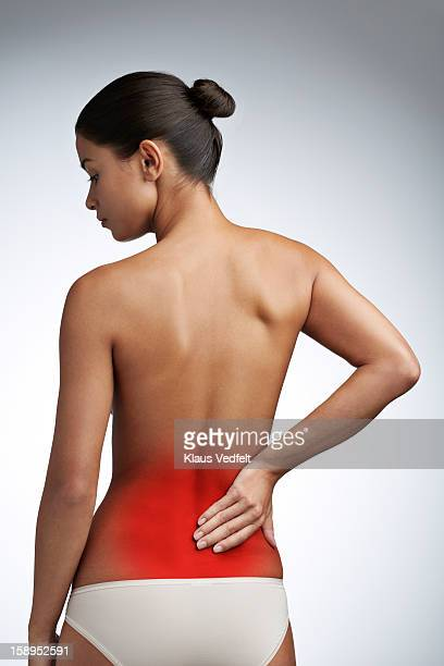 woman having lower back pain (rear view) - lower back - fotografias e filmes do acervo