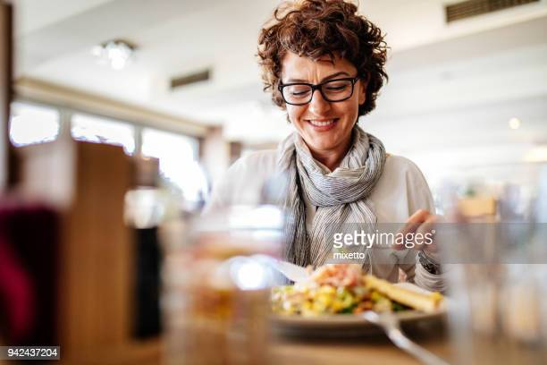 woman having lunch at a restaurant - one mature woman only stock pictures, royalty-free photos & images