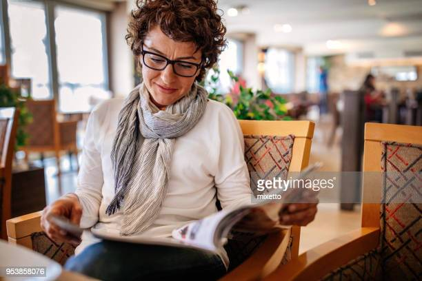 woman having lunch at a restaurant - magazine stock pictures, royalty-free photos & images