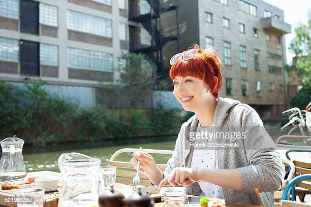 Woman having lunch by canal, East London, UK