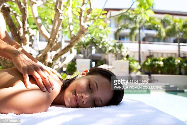 woman having massage by a resort pool - health farm - fotografias e filmes do acervo