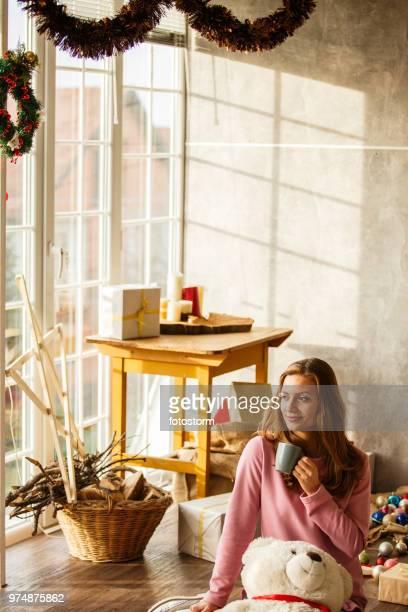 自宅で朝のコーヒーを持つ女性