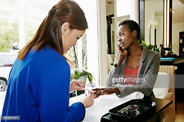 woman having nails done in salon - nail salon stock pictures, royalty-free photos & images