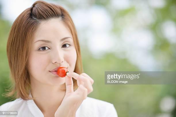 Woman having petit tomato