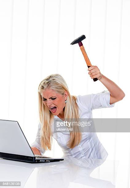 woman having problems with her computer is blowing with a hammer