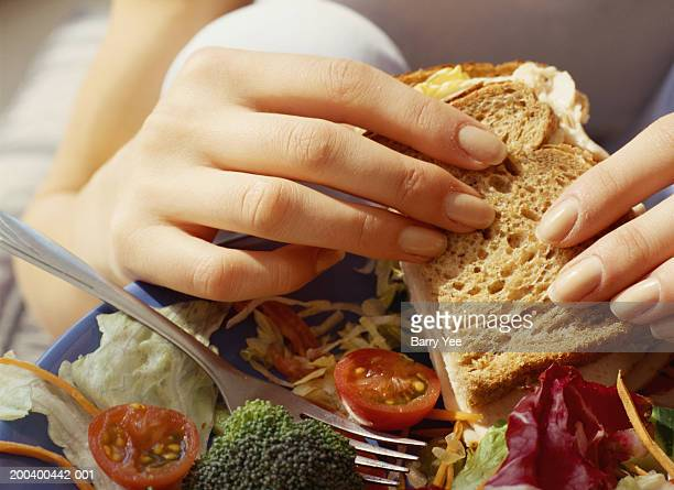 Woman having sandwich and salad, close-up