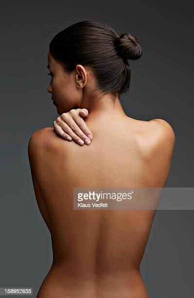 woman having shoulder pain (back view) - oben ohne frau stock-fotos und bilder